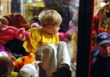 Ένα μικρό αγόρι μέσα σε μηχανή για παιχνίδια